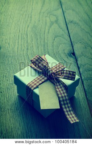 Single Gift Box With Gingham Ribbon And Blank Label On Wood - Cross Processed.