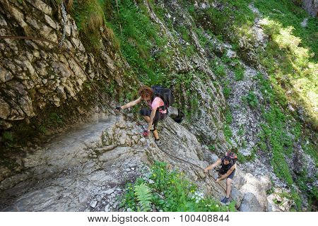 Hikers Climbing On A Safety Cable