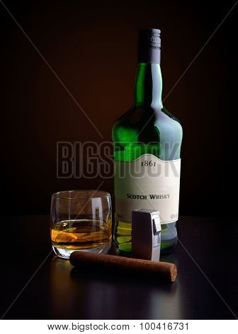 the bottle of whiskey and a glass of whiskey on a dark background