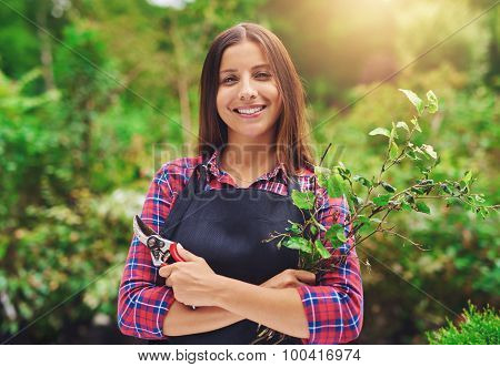 Smiling Young Female Gardener Pruning The Plants