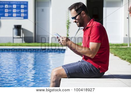 Man Reading Tablet Sitting On The Poolside.