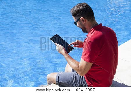 Man Using Tablet Sitting On The Poolside.
