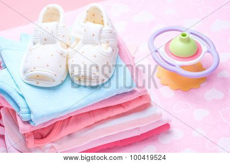 Cute Baby Shoes For Kids On Pile Of Baby Clothes.