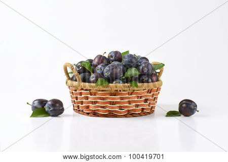 basket of ripe plums on white background