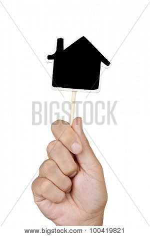 closeup of the hand of a young man holding a blank chalkboard in the shape of a house, against a white background