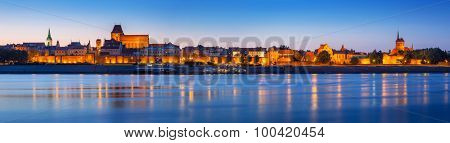 Panorama of Torun at night reflected in Vistula river, Poland
