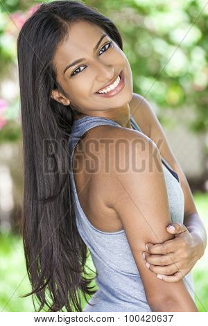 Outdoor portrait of a beautiful sporty Indian Asian young woman or girl outside in summer sunshine with perfect teeth and long hair