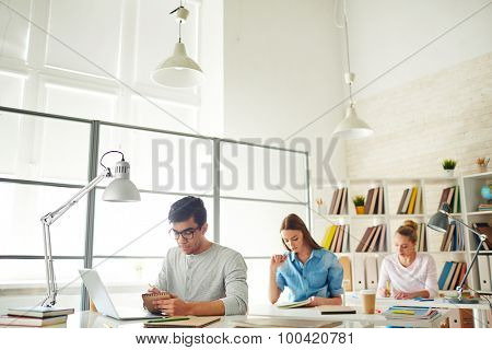 Group of teenagers sitting by desks and carrying out assignment
