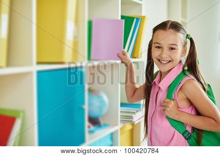 Cute schoolgirl with backpack looking at camera in library