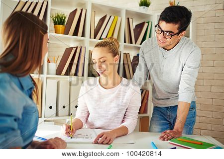 Cute teenage girl sitting by desk and drawing in notepad with her groupmates near by