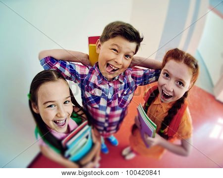 Group of joyful schoolkids with books looking at camera
