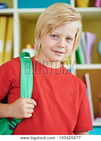 Happy pupil with backpack looking at camera