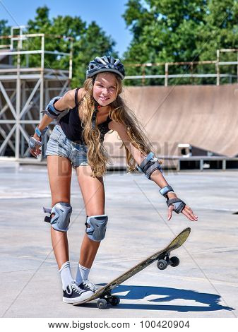 Girl with long hair skateboarding his skateboard outdoor.