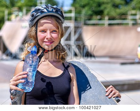 Teen skateboarding his skateboard outdoor. Girl drink water .