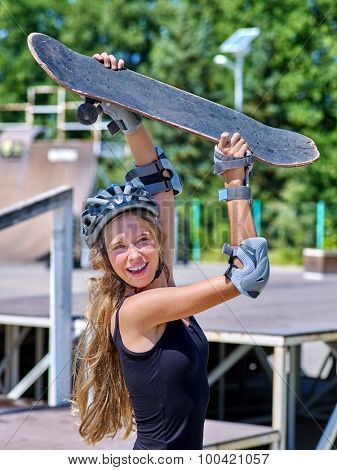 Teen skateboarding his skateboard outdoor. Girl holding  skate on his head.
