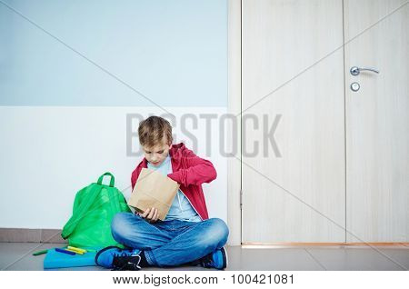 Schoolboy with paper pack taking out his lunch while sitting on the floor by classroom door