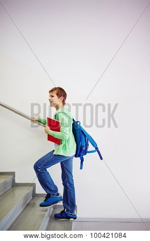 Pre-teen schoolboy with backpack going upstairs in school