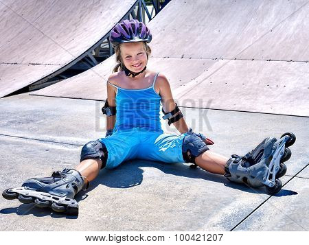Girl in roller skates sitting on ride in skatepark.