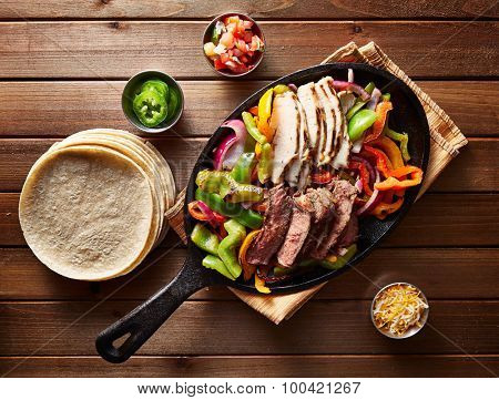 top down photo of mexican steak and chicken fajitas in iron skillet with corn tortillas