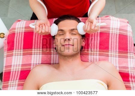 Man having relaxing herbal bag face massage in wellness spa