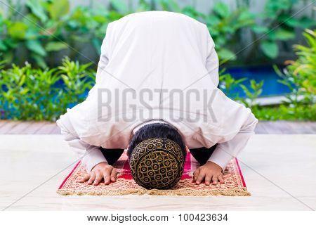 Asian Muslim man praying on carpet wearing traditional dress