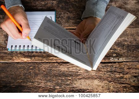 Man Reading A Book And Writes The Acquired Knowledge