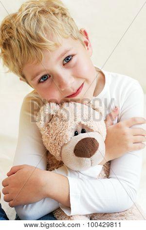 Cute Little Boy Hugs His Teddy Bear