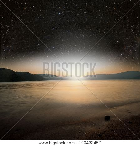 sun on a background star sky reflected in the sea. Elements of this image furnished by NASA
