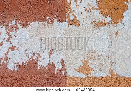 Abstract background of old vintage painted plastered wall with peeling paint and plaster texture in red orange colors