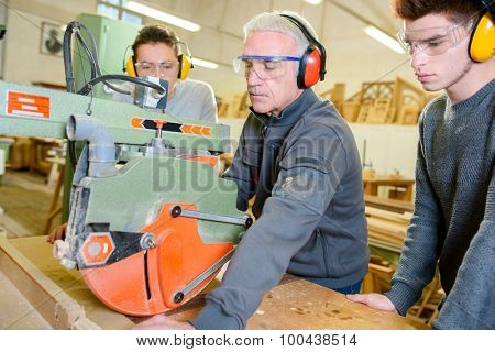 Carpenter teaching apprentices how to use a circular saw