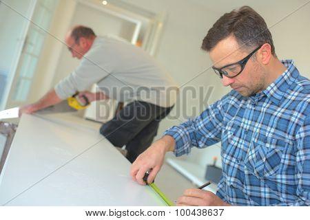 Carpenter using a tape measure