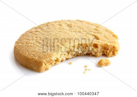 Single Round Shortbread Biscuit With Crumbs And Bite Missing. In Perspective.