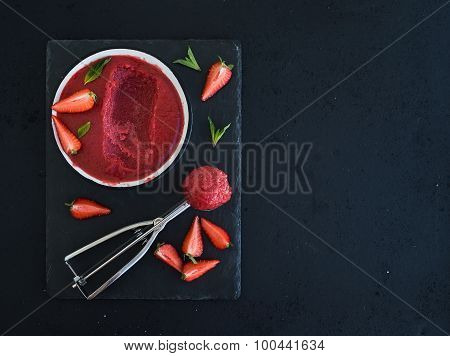 Strawberry sorbet or ice-cream with fresh berries, mint and metal scooper on black slate tray over d