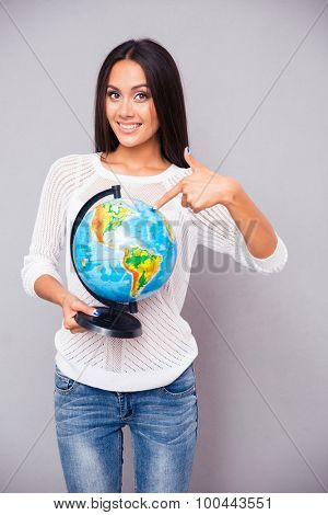 Happy young woman pointing finger at globe and looking at camera over gray background