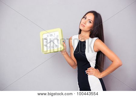 Portrait of a tired woman holding clock over gray background