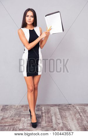 Full length portrait of a cute woman showing blank paper on gray background