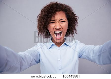 Afro american woman screaming and making selfie photo on gray background