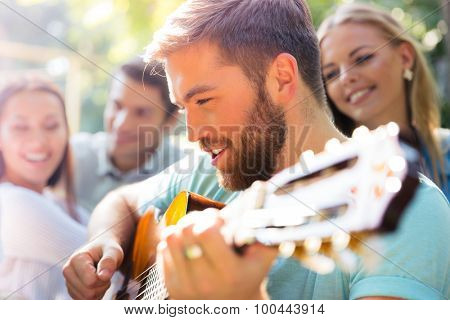 Group of cheerful friends with guitar having fun outdoor