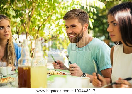 Group of a smiling friends sitting in outdoor restaurant
