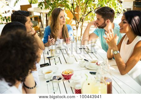 Smiling young friends enjoying meal in outdoor restaurant