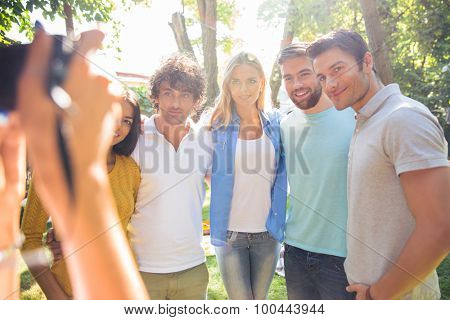 Female hands holding digital camera and making photo of a happy group friends