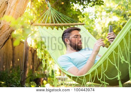 Handsome man lying on hammok and using smartphone outdoors