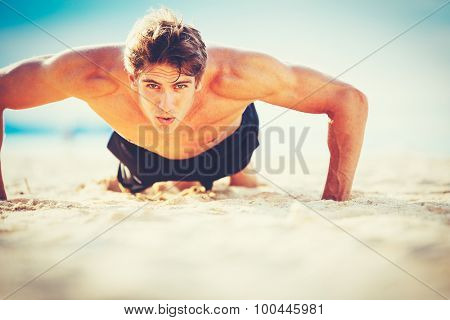 Fit young man doing push-ups on beach. Outdoor beach workout. Handsome young fitness man exercising. Sports and active lifestyle fitness concept.
