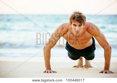 Fitness man doing push-ups on the beach. Male athlete exercising outdoors. Sports and active lifestyle.