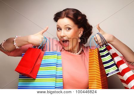 beautiful young woman with colored shopping bags over grey background