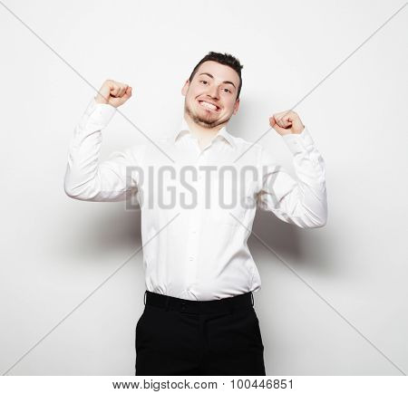 life style, business  and people concept: successful businessman. Happy young man in formalwear gesturing and smiling while standing against white background