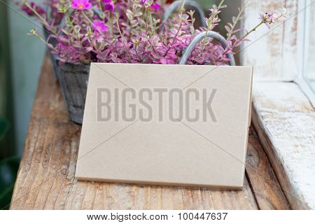 Cardboard With Blank Area For Your Text And Flowers Behind It