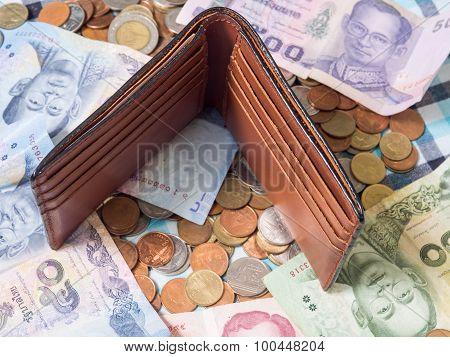Brown Leather Wallet Put On The Pile Of Banknotes And Coins Baht Currency Background.