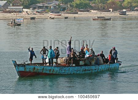 Several African Men Floating In Boat Along The Shore.