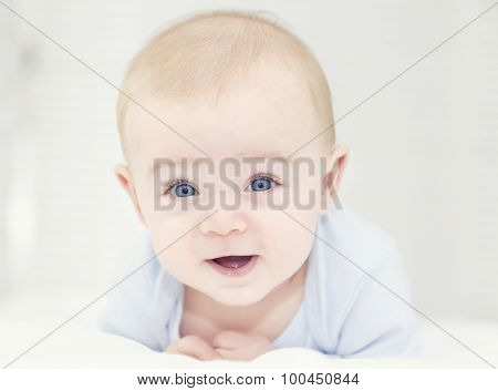 Baby with blue eyes looking to the camera and smiling
